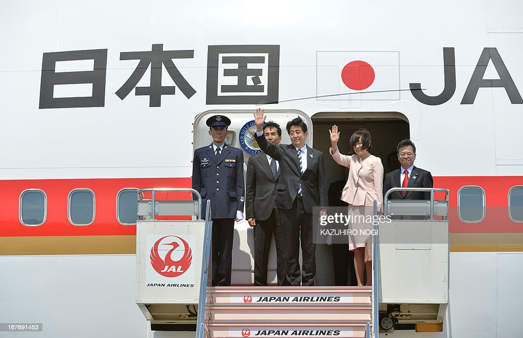 Japanese Prime Minister Shinzo Abe (C) and his wife Akie (2nd R) wave to well-wishers upon his departure at Tokyo's Haneda airport on April 28, 2013. Abe left for Russia and he will also visit to Saudi Arabia, the United Arab Emirates and Turkey on a weeklong trip.