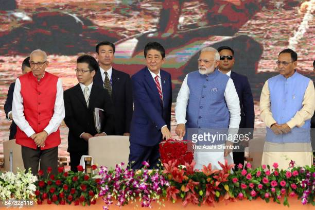 Japanese Prime Minister Shinzo Abe and Indian Prime Minister Narendra Modi push the button during the groundbreaking ceremony of the high speed train...