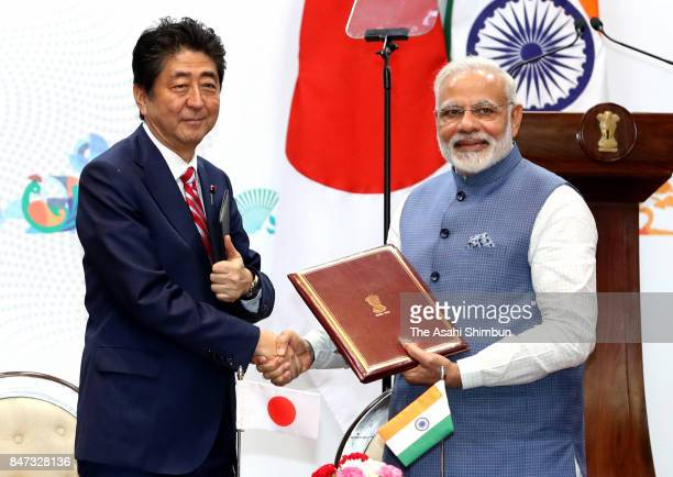 Japanese Prime Minister Shinzo Abe and Indian Prime Minister Narendra Modi exchange signed documents after the signing ceremony following their...