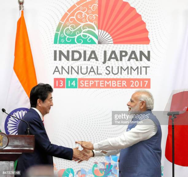 Japanese Prime Minister Shinzo Abe and Indian Prime Minister Narendra Modi shake hands after a joint press conference following their summit meeting...
