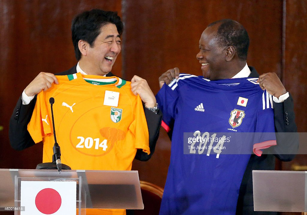 Japanese Prime Minister <a gi-track='captionPersonalityLinkClicked' href=/galleries/search?phrase=Shinzo+Abe&family=editorial&specificpeople=559017 ng-click='$event.stopPropagation()'>Shinzo Abe</a> (L) and Ivory Coast President <a gi-track='captionPersonalityLinkClicked' href=/galleries/search?phrase=Alassane+Ouattara&family=editorial&specificpeople=697562 ng-click='$event.stopPropagation()'>Alassane Ouattara</a> exchange their football national teams' uniforms during their summit meeting on January 10, 2014 in Abidjan, Ivory Coast. Abe is on tour to Oman, Ivory Coast, Mozambique and Ethiopia.