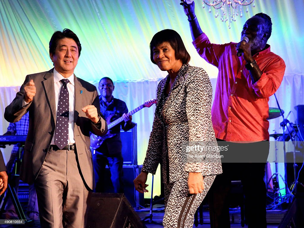 Japanese Prime Minister <a gi-track='captionPersonalityLinkClicked' href=/galleries/search?phrase=Shinzo+Abe&family=editorial&specificpeople=559017 ng-click='$event.stopPropagation()'>Shinzo Abe</a> (L) and Jamaican Prime Minister Portia Simpson-Miller (C) dance to reggae singer Freddie McGregor (R) during the welcome dinner at Simpson-Miller's official residence on September 30, 2015 in Kingston, Jamaica. Prime Minister Abe is on tour to the United States to attend the United Nations General Assembly followed by the visit to Jamaica.