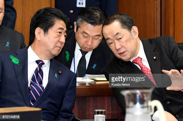 Japanese Prime Minister Shinzo Abe and Justice Minister Katsutoshi Kaneda chat before the House of Representatives judicial affairs committee begins...