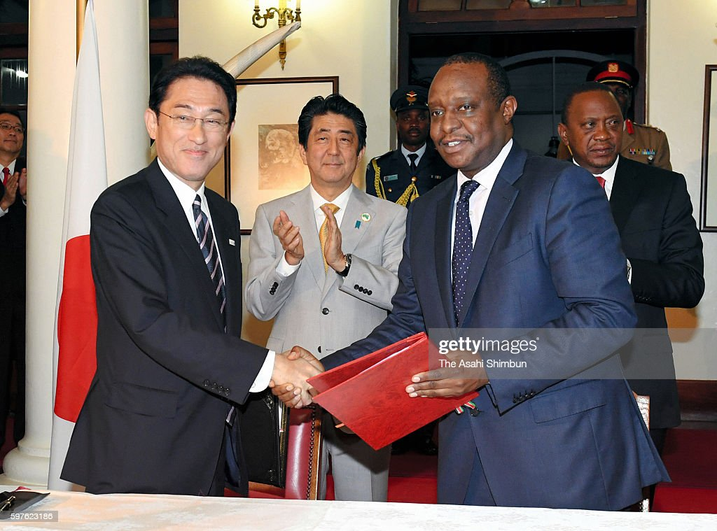 Japanese Prime Minister Shinzo Abe and Kenyan President Uhuru Kenyatta applaud as Japanese Foreign Minister Fumio Kishida and exchages the agreement...