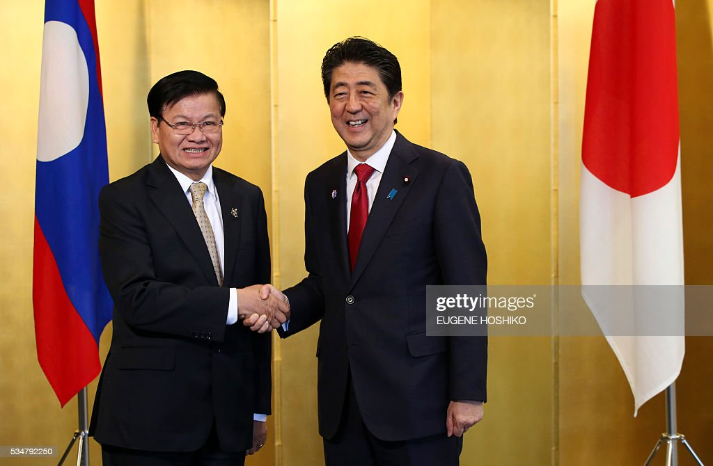 Japanese Prime Minister Shinzo Abe(R) and Laos' Prime Minister Thongloun Sisoulith(L) shake hands prior to the their meeting in Nagoya, in central Japan on May 28, 2016. Sisoulith is in Japan to attend the G-7 Ise-Shima summit outreach session. / AFP / POOL / Eugene Hoshiko
