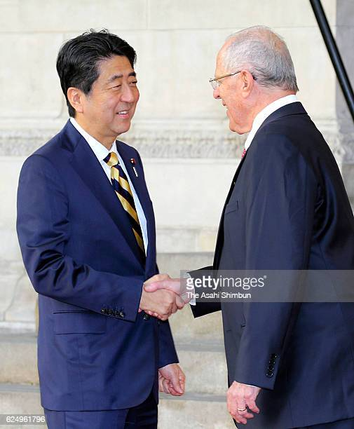 Japanese Prime Minister Shinzo Abe and Peruvian President Pedro Pablo Kuczynski shake hands during the welcome ceremony on November 18 2016 in Lima...