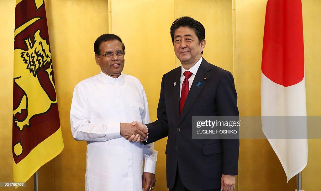 Japanese Prime Minister Shinzo Abe (R) and Sri Lanka's President Maithripala Sirisena (L) shake hands prior to the their meeting in Nagoya, central Japan on May 28, 2016. / AFP / POOL / Eugene Hoshiko