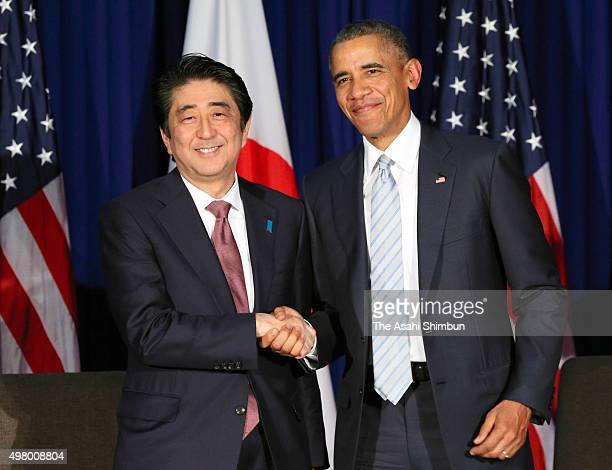 Japanese Prime Minister Shinzo Abe and US President Barack Obama shake hands during their bilateral meeting on the sidelines of the Asia Pacific...