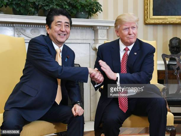 Japanese Prime Minister Shinzo Abe and US President Donald Trump shake hands ahead of their talks at the White House in Washington on Feb 10 2017