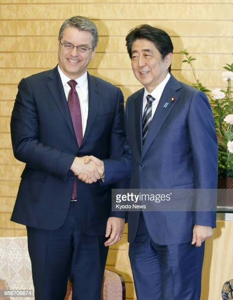 Japanese Prime Minister Shinzo Abe and World Trade Organization Director General Roberto Azevedo shake hands in Tokyo on May 22 2017 Japan and the...