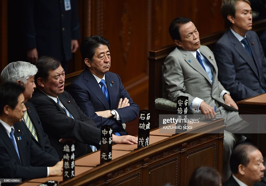 Japanese Prime Minister Shinzo Abe (C) ane his cabinet members attend a plenary session of the House of Representatives at the end of 150-day regular Diet session on June 1, 2016. Japanese leader Shinzo Abe is set to announce June 1 that he will delay a consumption tax hike and launch another blast of government spending, underscoring his failure to ignite the limp economy, analysts said. / AFP / KAZUHIRO