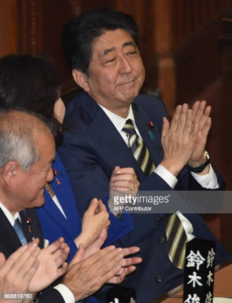 Japanese Prime Minister Shinzo Abe applauds at the lower house of parliament in Tokyo on November 1 2017 Japan's parliament formally reelected Abe as...