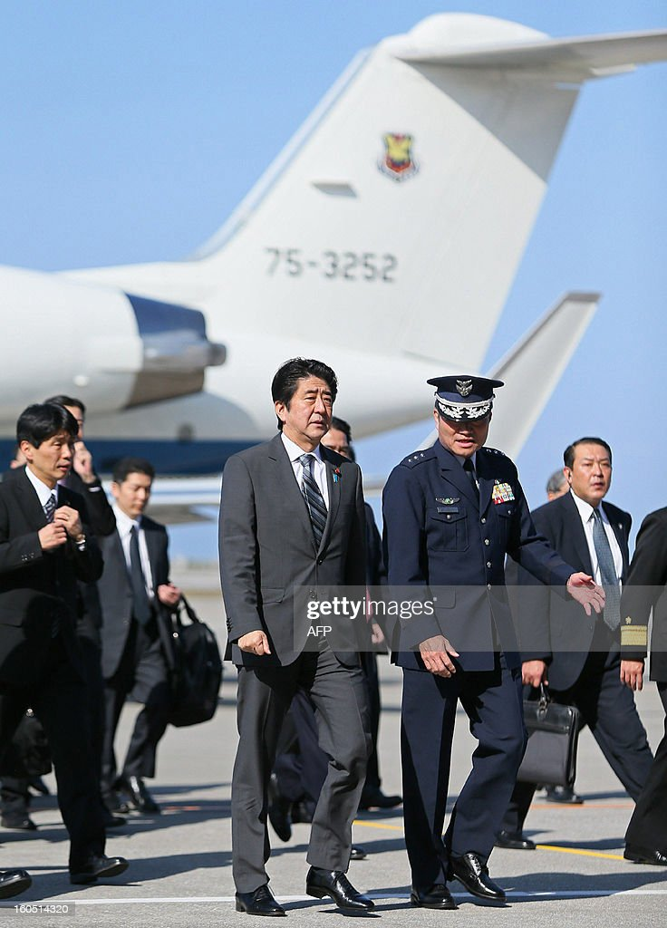 Japanese Prime Minister Shinzo Abe arrives at Naha air base in Japan's southern island of Okinawa on February 2, 2013 for the first visit to Okinawa since becoming premier in December. Abe vowed to defend Japan against 'provocations' as he toured the southern region of Okinawa near islands at the centre of a boiling territorial dispute with China. AFP PHOTO / JIJI PRESS JAPAN OUT