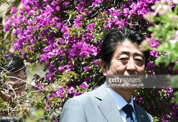 Japanese Prime Minister Shinzo Abe arrives to pose for a family photo with other participants of the G7 summit during the Summit of the Heads of...