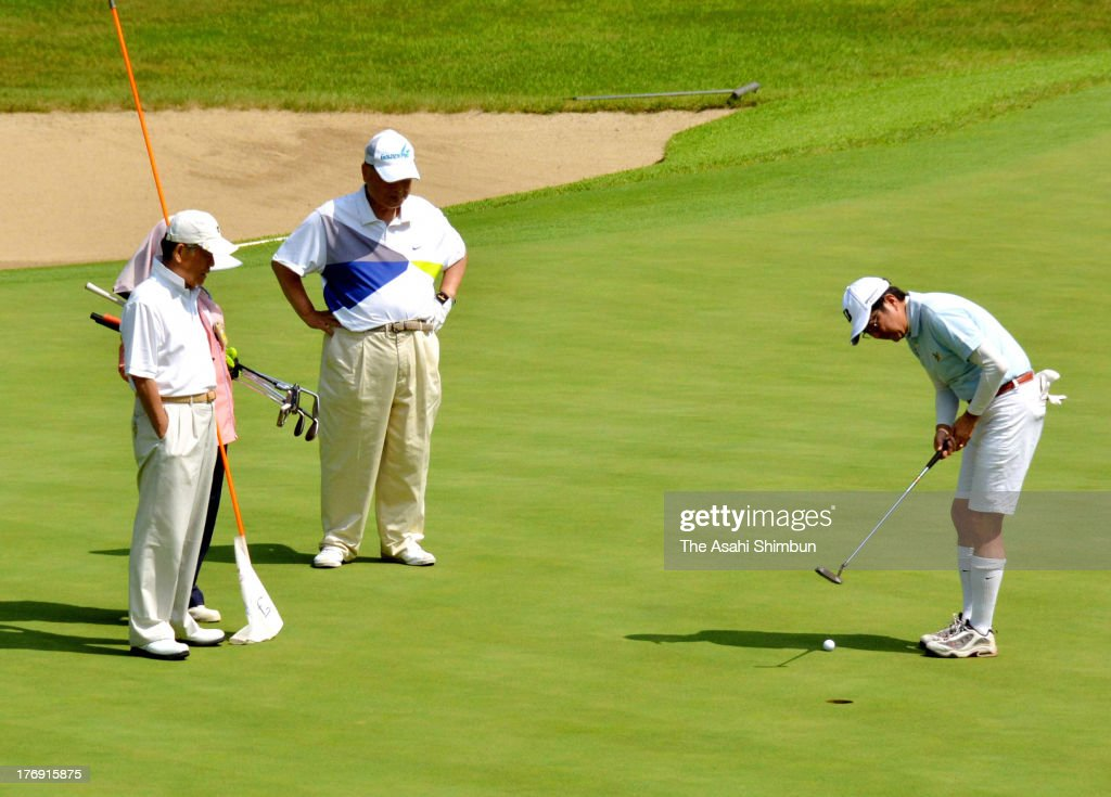 Japanese Prime Minister Shinzo Abe (1st R) attempts a putt while former Prime Minister Yoshiro Mori (C) watches during their holiday on August 16, 2013 in Fujikawaguchiko, Yamanashi, Japan.