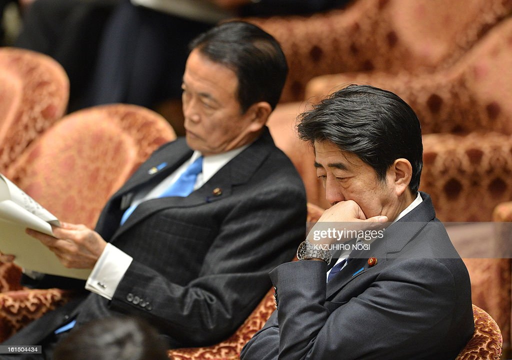 Japanese Prime Minister Shinzo Abe (R) attends a budget committee session of the lower house at parliament in Tokyo on February 12, 2013.