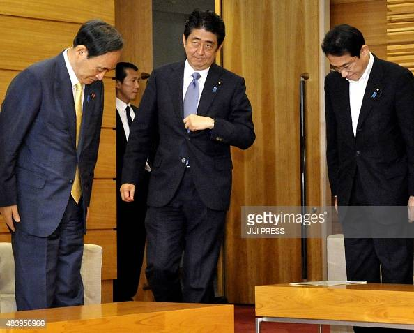 Japanese Prime Minister SHinzo Abe attends a cabinet meeting while Chief Cabinet Secretary Yoshihide Suga and Foreign Minister Fumio Kishida bow...