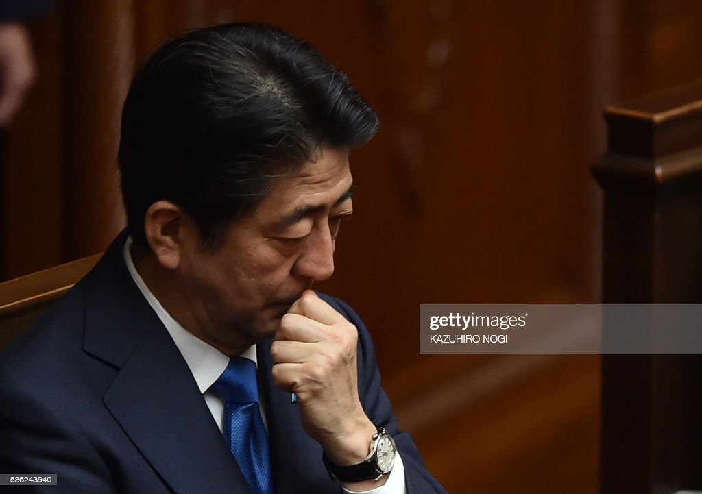 Japanese Prime Minister Shinzo Abe attends a plenary session of the House of Representatives at the end of 150-day regular Diet session on June 1, 2016. Japanese leader Shinzo Abe is set to announce June 1 that he will delay a consumption tax hike and launch another blast of government spending, underscoring his failure to ignite the limp economy, analysts said. / AFP / KAZUHIRO