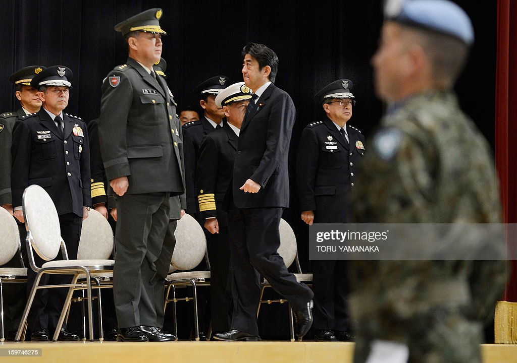Japanese Prime Minister Shinzo Abe (C) attends flag return ceremony for the the United Nations assigned Japanese platoon at the Defence Ministry in Tokyo on January 20, 2013. All Japanese soldiers recently returned from United Nations peacekeeping operations assignment in the Golan Heights. AFP PHOTO/Toru YAMANAKA