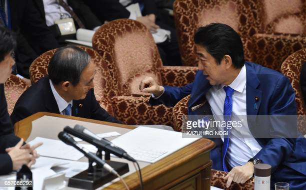 Japanese Prime Minister Shinzo Abe chats with Chief Cabinet Secretary Yoshihide Suga during a budget committee session of the House of Councilors at...