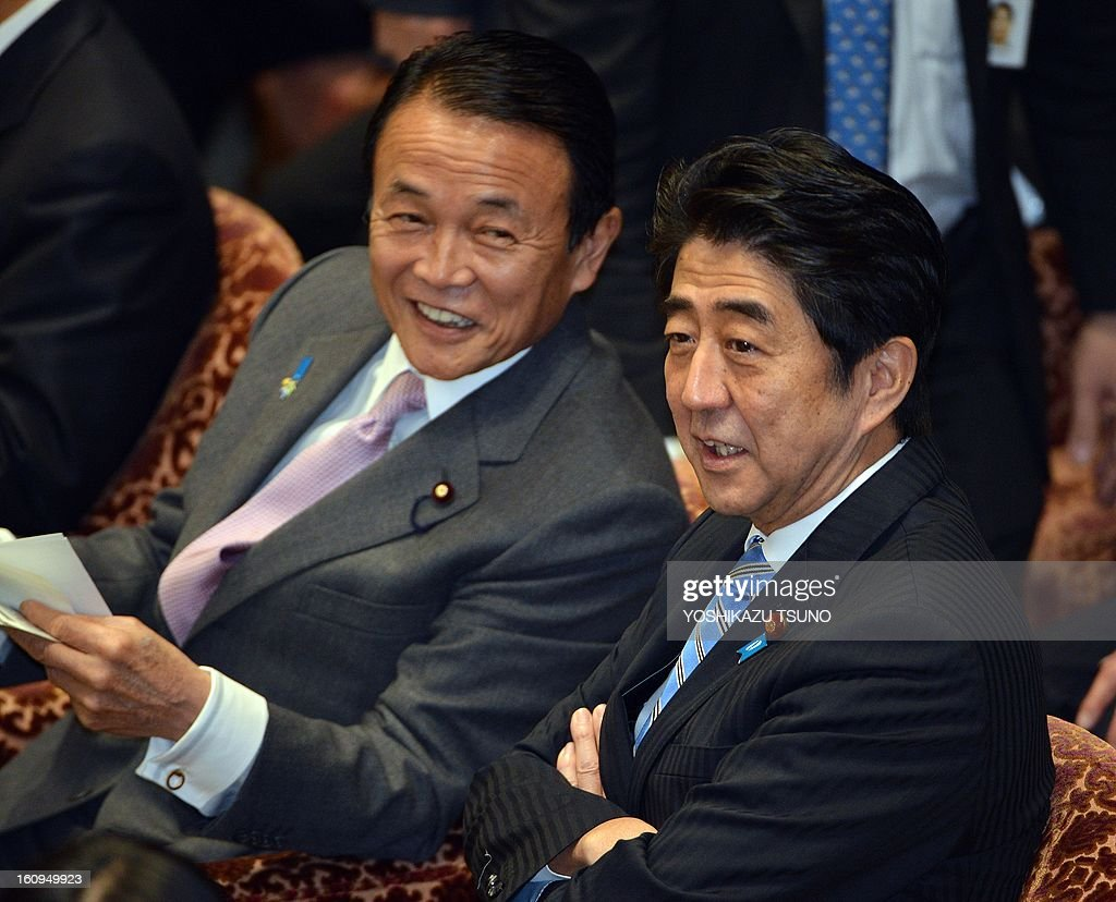 Japanese Prime Minister Shinzo Abe (R) chats with Finance Minister Taro Aso (L) before starting the Lower House's budget committee session at the National Diet in Tokyo on February 8, 2013. Abe will not announce whether Japan will join the TPP free trade negotiations when he visits the US in this month for talks with President Barack Obama government sources said on February 7. AFP PHOTO / Yoshikazu TSUNO
