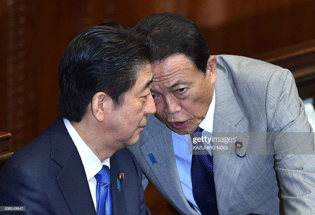 Japanese Prime Minister Shinzo Abe (L) chats with Finance Minister Taro Aso during a plenary session of the House of Representatives at the end of 150-day regular Diet session on June 1, 2016. Japanese leader Shinzo Abe is set to announce June 1 that he will delay a consumption tax hike and launch another blast of government spending, underscoring his failure to ignite the limp economy, analysts said. / AFP / KAZUHIRO