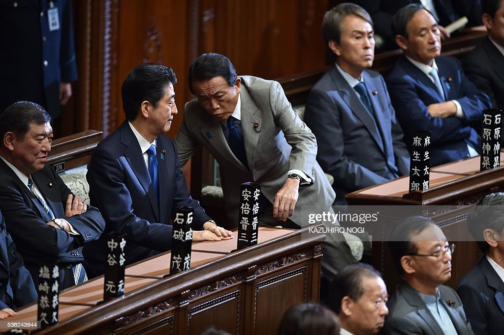 Japanese Prime Minister Shinzo Abe (2nd L) chats with Finance Minister Taro Aso (C) during a plenary session of the House of Representatives at the end of 150-day regular Diet session on June 1, 2016. Japanese leader Shinzo Abe is set to announce June 1 that he will delay a consumption tax hike and launch another blast of government spending, underscoring his failure to ignite the limp economy, analysts said. / AFP / KAZUHIRO