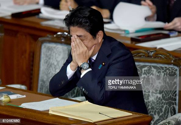Japanese Prime Minister Shinzo Abe covers his face with his hands after delivering a policy speech at the plenary session of the lower house of...