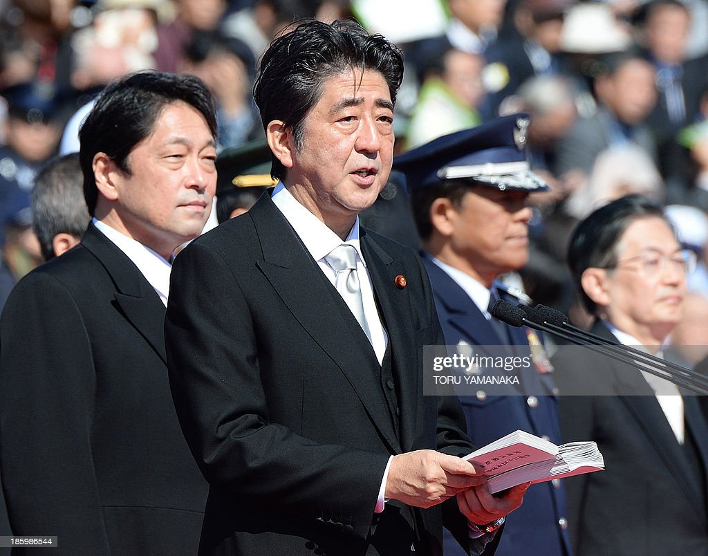 Japanese Prime Minister Shinzo Abe (C) delivers a speech beside Defence Minister Itsunori Onodera (L) during the military review at the Ground Self-Defence Force's Asaka training ground on October 27, 2013. Around 3,900 personnel, 240 armoured vehicles and 50 aircrafts took part in the inspection parade. AFP PHOTO / Toru YAMANAKA