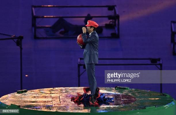 TOPSHOT Japanese Prime Minister Shinzo Abe dressed as Super Mario holds a red ball during the closing ceremony of the Rio 2016 Olympic Games at the...