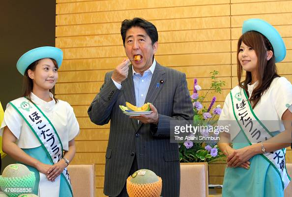 Japanese Prime Minister Shinzo Abe eats a slice of melon specialty of Hokota City during his meeting with Hokota Brand Ambassadors at his official...