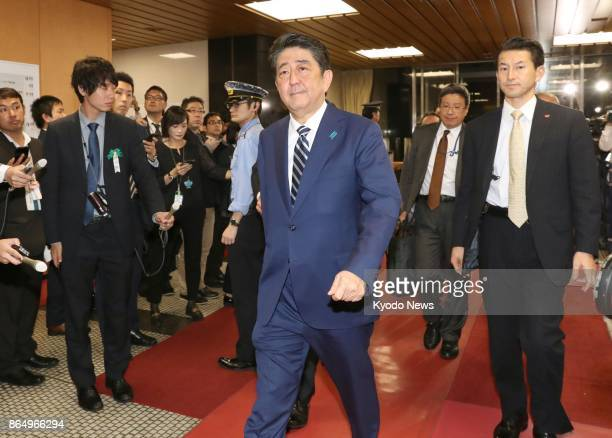 Japanese Prime Minister Shinzo Abe enters the headquarters of his ruling Liberal Democratic Party in Tokyo just before polls close for the House of...