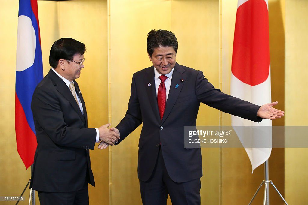 Japanese Prime Minister Shinzo Abe(R) escorts Laos' Prime Minister Thongloun Sisoulith(L) to the their meeting in Nagoya, in central Japan on May 28, 2016. Sisoulith is in Japan to attend the G-7 Ise-Shima summit outreach session. / AFP / POOL / Eugene Hoshiko