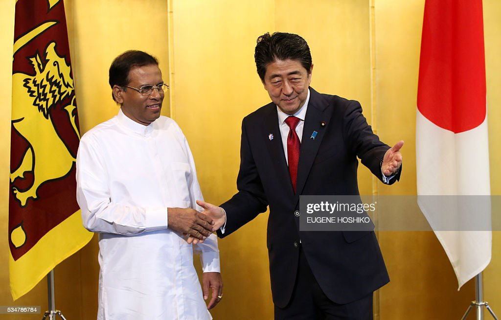 Japanese Prime Minister Shinzo Abe (R) escorts Sri Lanka's President Maithripala Sirisena (L) to the their meeting in Nagoya, central Japan on May 28, 2016. / AFP / POOL / Eugene Hoshiko