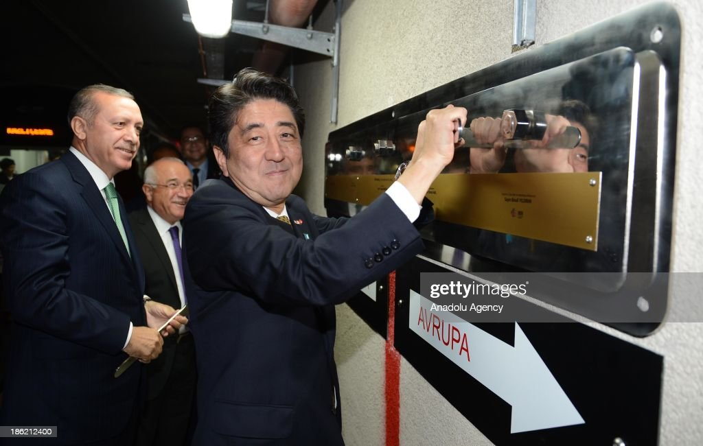 Japanese Prime Minister Shinzo Abe (R) fastens a board as Turkish Prime Minister Recep Tayyip Erdogan (L) lokks next to the red line representatively connecting Europe and Asia, after the inauguration ceremony of the Marmaray, the railway tunnel underneath the Bosphorus Strait linking European and Asian sides of Istanbul, on October 29, 2013 Istanbul, Turkey.