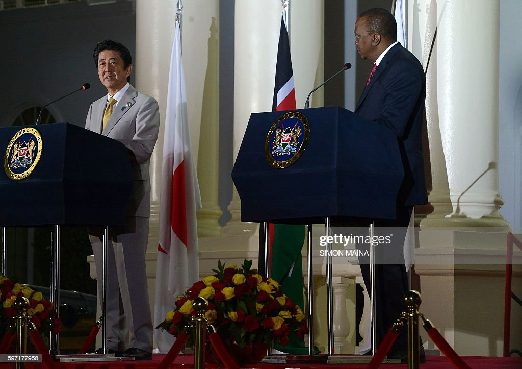 Japanese Prime Minister Shinzo Abe flanked by Kenya's President Uhuru Kenyatta speaks during a joint press conference at the State House at the end...