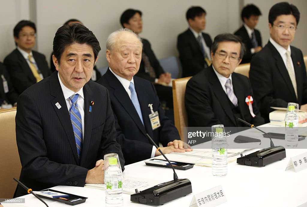 Japanese Prime Minister Shinzo Abe (L), flanked by the chair member Shunji Yanai (2nd L) and other the panel members, attends an advisory panel on restructuring legal infrastructure of security guarantees at Abe's official residence in Tokyo on February 8, 2013. AFP PHOTO / Issei Kato / POOL