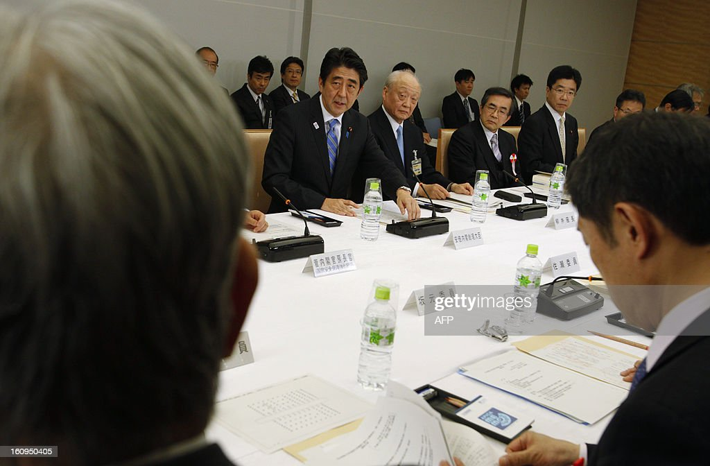 Japanese Prime Minister Shinzo Abe (C), flanked by the chair member Shunji Yanai (C-R) and other the panel members, attends an advisory panel on restructuring legal infrastructure of security guarantees at Abe's official residence in Tokyo on February 8, 2013. AFP PHOTO / Issei Kato / POOL