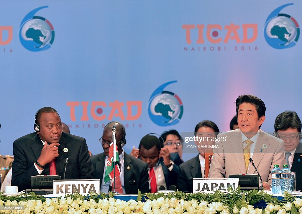 Japanese Prime Minister Shinzo Abe gives his closing remarks as Kenya's President Uhuru Kenyatta looks on along with other dignitaries at the end of...