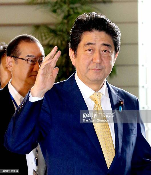 Japanese Prime Minister Shinzo Abe greets to media reporters on arrival at his official residence on July 16 2015 in Tokyo Japan The ruling coalition...