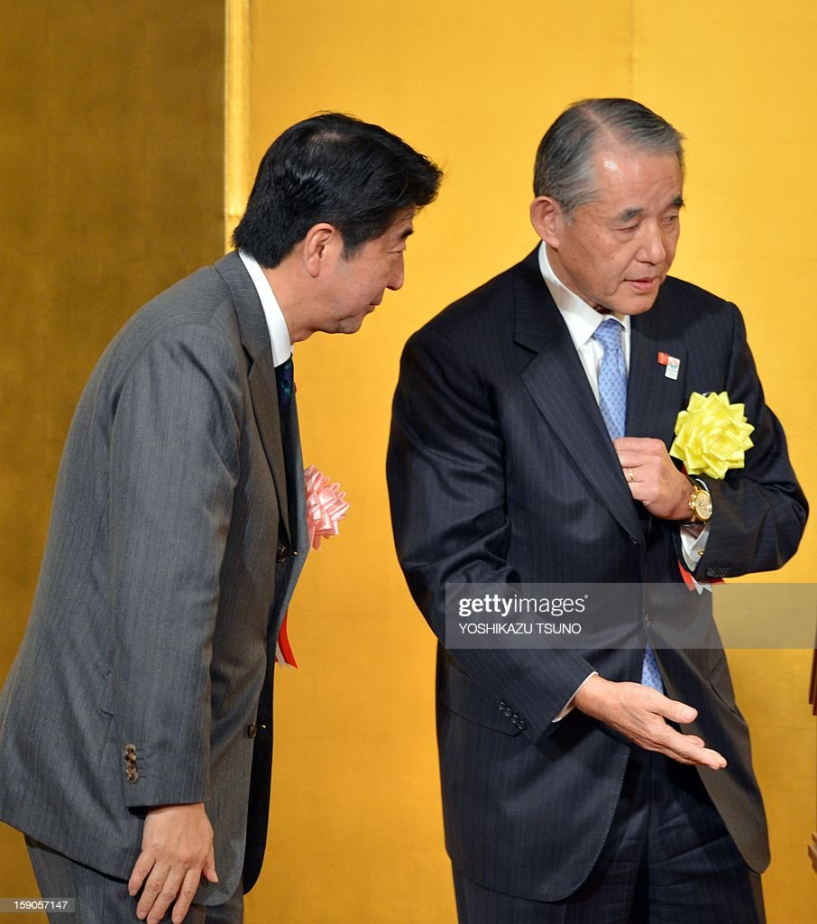 Japanese Prime Minister Shinzo Abe (L) is greeted by Yasuchika Hasegawa (R), chairman of Keizai Doyukai (the Japan Association of Corporate Executives), as he speaks before Japan's business leaders at a New Year's party at a Tokyo hotel on January 7, 2013. Japan's major business lobbies said they support Prime Minister Abe for his efforts to revive the dwindling economy, urging him an early participation in a Pacific-wide free trade deal. AFP PHOTO / Yoshikazu TSUNO