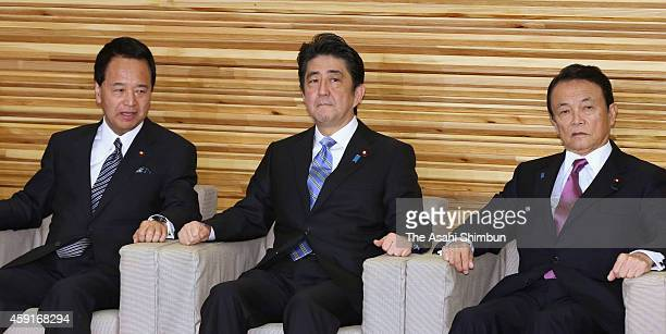 Japanese Prime Minister Shinzo Abe is seen with Economic Revitalization Minister Akira Amari and Finance Minister Taro Aso during a cabinet meeting...