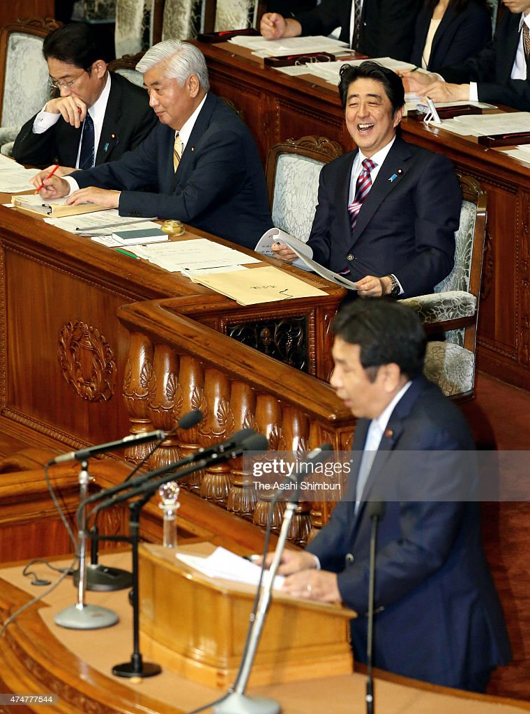 Japanese Prime Minister Shinzo Abe laughs as opposition Democratic Party of Japan secretary general Yukio Edano questions on the controversial national security legislation bill during the lower house plenary session of the diet on May 26, 2015 in Tokyo, Japan. Remarks by Abe administration officials on the possibility of Japan attacking enemy bases sparked confusion before nuts-and-bolts deliberations on national security legislation began in the Diet. The legislation is designed to expand Japan's security role around the world and allow the nation to exercise the right to collective self-defense, a measure that had been banned until the Abe Cabinet reinterpreted the war-renouncing Constitution in July 2014.