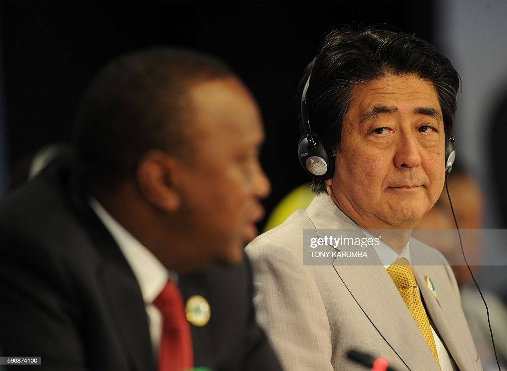Japanese Prime Minister Shinzo Abe listens as Kenya's President Uhuru Kenyatta delivers his closing remarks at the end of the sixth Tokyo...
