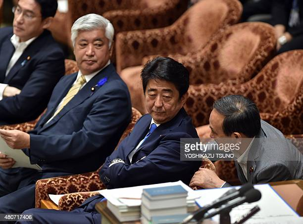 Japanese Prime Minister Shinzo Abe listens to Chief Cabinet Secretary Yoshihide Suga while Defence Minister Gen Nakatani and Foreign Minister Fumio...