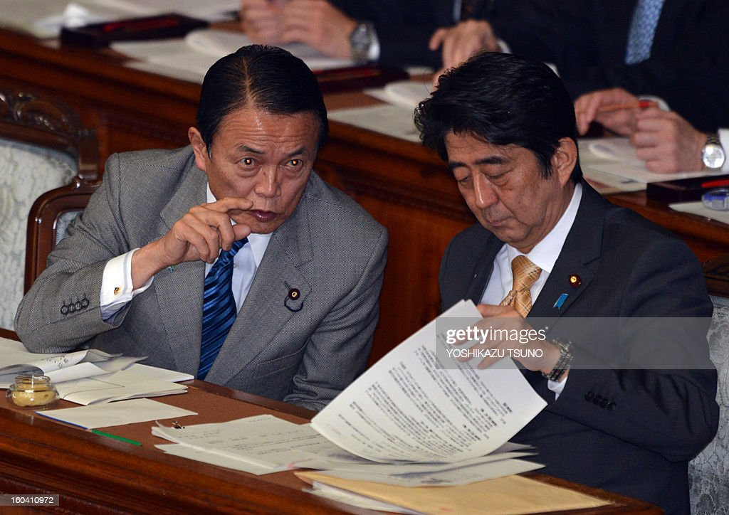 Japanese Prime Minister Shinzo Abe (R) listens to Finance Minister Taro Aso (L) at the Lower House's plenary session at the National Diet in Tokyo on January 31, 2013. Japan's hawkish Prime Minister Shinzo Abe told parliament January 31 that he intends to change the country's post-World War II constitution, lowering the bar for further amendments. AFP PHOTO / Yoshikazu TSUNO