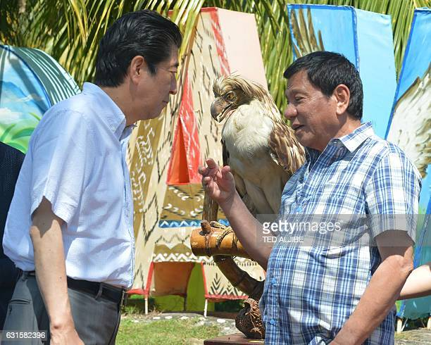 Japanese Prime Minister Shinzo Abe listens to smiles Philippine President Rodrigo Duterte during the naming of Philippine eagle ceremony at a hotel...