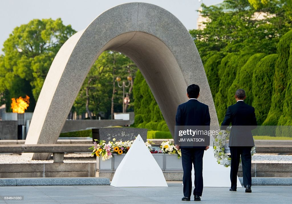 Japanese Prime Minister Shinzo Abe (L) looks on as US President Barack Obama (R) lays a wreath at the Hiroshima Peace Memorial Park in Hiroshima on May 27, 2016. Obama on May 27 paid moving tribute to victims of the world's first nuclear attack. WATSON