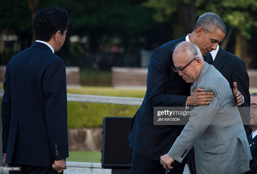 Japanese Prime Minister Shinzo Abe (L) looks on as US President Barack Obama (2nd R) hugs a survivor of the 1945 atomic bombing of Hiroshima, during a visit to the Hiroshima Peace Memorial Park on May 27, 2016. Obama on May 27 paid moving tribute to victims of the world's first nuclear attack. WATSON