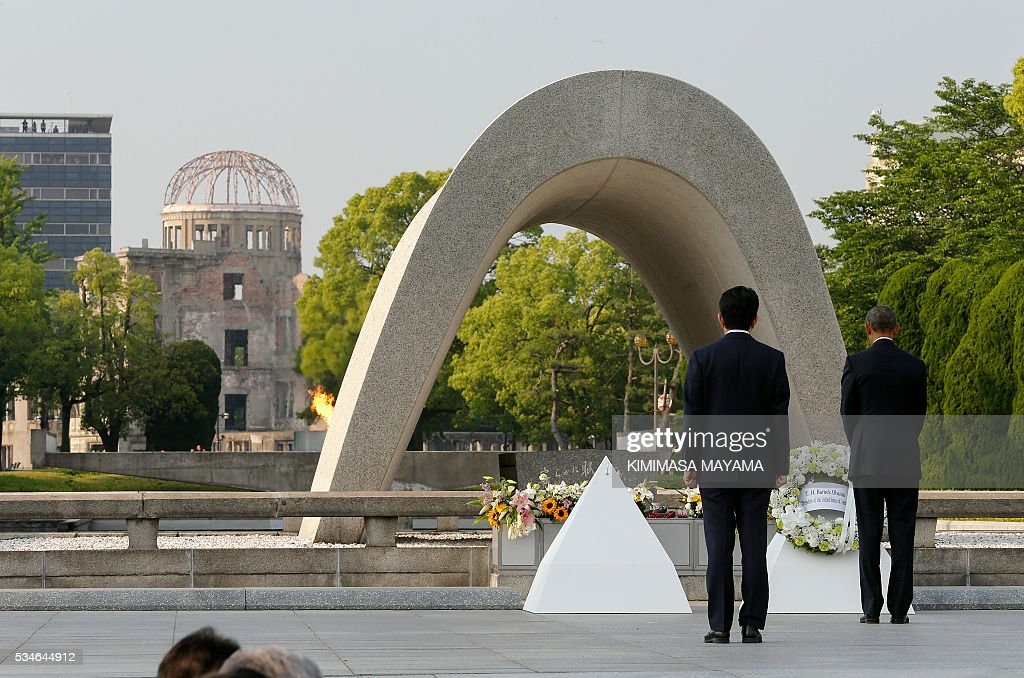 Japanese Prime Minister Shinzo Abe (2nd R) looks on as US President Barack Obama (R) lays a wreath during a visit to the Hiroshima Peace Memorial Park in Hiroshima on May 27, 2016. Obama on May 27 paid moving tribute to victims of the world's first nuclear attack. MAYAMA